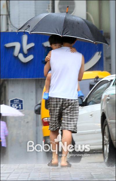 베이비뉴스 이기태 기자 = 12일 오전 장대비가 내리는 가운데 서울 구로구 구로동 한 소아과 의원 앞에서 한 아빠가 아픈 자녀 아이와 함께 진료를 마치고 약국에서 약을 받아 우산을 쓰고 귀가하고 있다. likitae@ibabynews.com ⓒ베이비뉴스