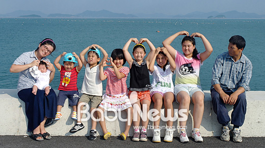 베이비뉴스 신은희 기자 = 전남 장흥군 회진면 노력항을 배경으로 김영덕 지에코 씨 부부가 7남매와 함께 '사랑해요'라며 하트를 만들어 보이고 있다. euni@ibabynews.com ⓒ베이비뉴스