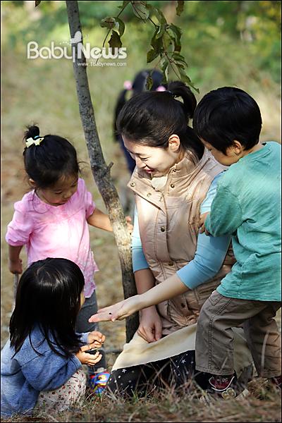 베이비뉴스 이기태 기자 = 성미산어린이집 아마 활동에 나선 김주현(펭귄, 38) 씨가26일 오전 서울 마포구 성미산어린이집 뒷산인 성미산에서 성미산어린이집 아이들과 함께 마술놀이를 하고 있다. 아마(아빠 + 엄마) 활동 중 하나인 일일 보육교사 활동은 보육교사가 휴가 가는 날에 부모가 그 보육실 아이들을 맡아서 하루를 지내는 일일 보육교사 활동을 말한다. likitae@ibabynews.com ⓒ베이비뉴스