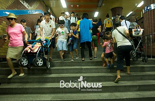 8월 13일 오후 서울 용산구 동자동 지하철 1호선↔4호선 환승구간 계단에서 한 부부(왼쪽)가 자녀를 태운 유모차를 들고 4호선 방향으로 내려오고 있다. 그 옆으로는 또 다른 한 엄마가 유모차를 들고 1호선 방향으로 오르고 있다. 유모차에서 내려 걸어 올라가던 동생을 누나가 안아주고 있는 모습도 보인다. 이기태 기자 likitae@ibabynews.com ⓒ베이비뉴스