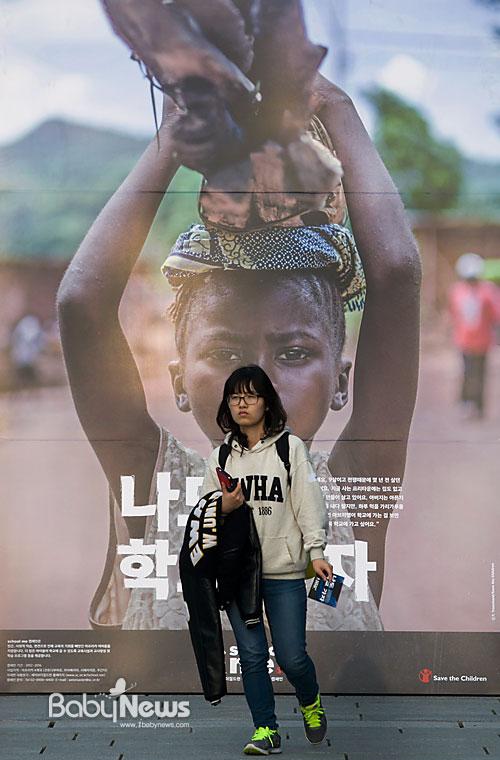 국제구호개발 NGO 세이브더칠드런이 아동권리주간을 맞아 15일 오후 서울 서대문구 대현동 이화여자대학교 ECC 밸리에서 아프리카 여아 학교보내기 'School Me' 캠페인 론칭 행사를 열었다. 이화여자대학교 한 여학생이 백팩을 메고 대형 포스터 앞을 지나가고 있다. 이기태 기자 likitae@ibabynews.com ⓒ베이비뉴스