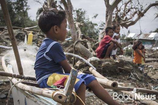파나이 섬에 살고 있는 조셉(5)이 집 앞 해안가에서 이웃 주민의 배 위에 앉아 있다. 태풍 하이옌으로 생계수단인 배를 잃은 조셉네 가족은 세이브더칠드런의 현금 지원(Cash Grant)을 통해 새 배를 살 수 있게 됐다. ⓒ세이브더칠드런