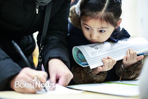 서울시 공립초등학교 2017학년도 입학생 예비소집날인 11일 오후 서울 마포 염리초등학교에서 입학 예정인 아이가 엄마가 입학등록 서류 작성하는 것을 빤히 바라보고 있다. 이기태 기자 ⓒ베이비뉴스