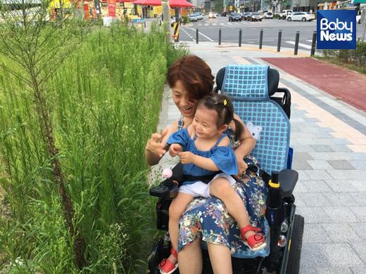 김민정 씨와 그의 딸 최고은 양. 김 씨는 때로 딸을 전동휠체어 위에 태우고 이동한다. ⓒ김민정